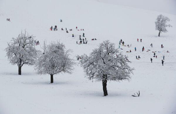 Lidé sáňkují během prvního sněhu v Albis Passu, Švýcarsko - Sputnik Česká republika