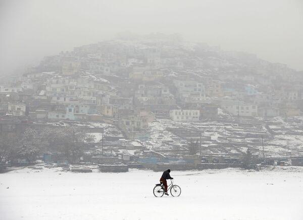 Cyklista během sněžení uprostřed zasněženého Kábulu, Afghánistán - Sputnik Česká republika