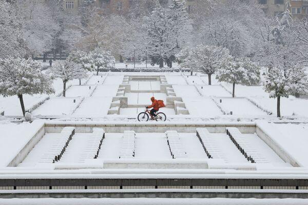 Muž na kole během sněžení v Sofii, Bulharsko - Sputnik Česká republika