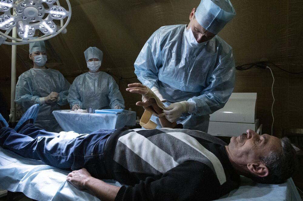 Lékař pomáhá pacientovi v polní nemocnici