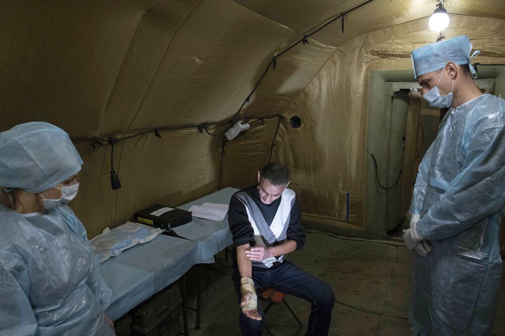 Lékaři poskytují pomoc pacientovi v polní nemocnici