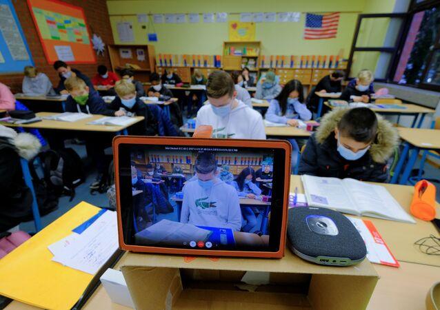 Studenti navštěvují virtuální výuku angličtiny, kterou provádí učitel v domácí karanténě v Německu