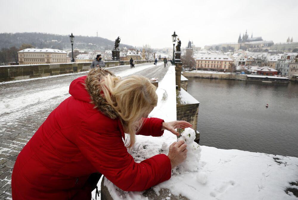 Žena staví sněhuláka na Karlově mostě
