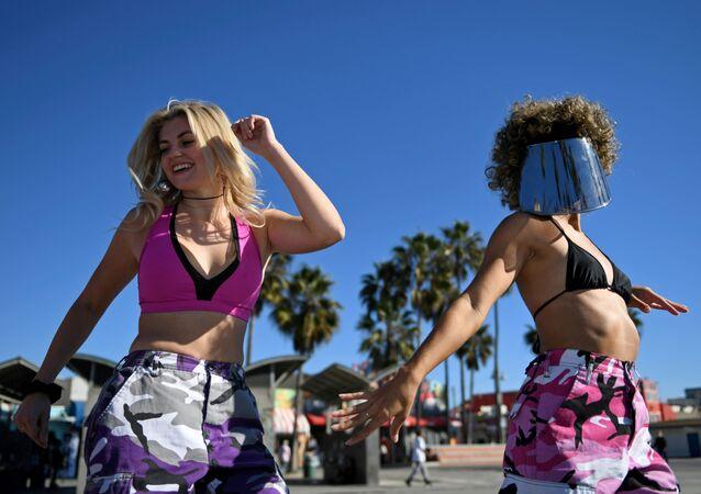 Dívky na pláži v Los Angeles den před rozvolňováním protikoronavirových opatření.