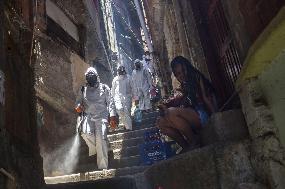 Dobrovolník provádí dezinfekci ve favelách, Rio de Janeiro.