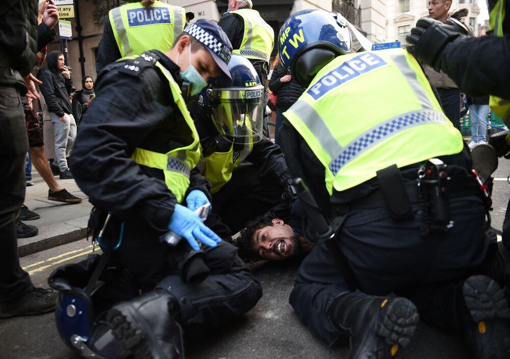 Policie provádí zásah na demonstraci proti omezujícím protikoronavirovým opatřením v Londýně.