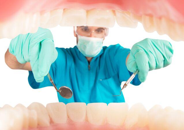 Zubař zkoumá ústní dutinu pacienta
