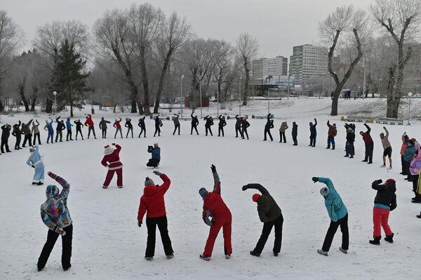 Lidé cvičí na břehu zamrzlé řeky Irtyš během zahájení zimní plavecké sezóny v ruském Omsku. - Sputnik Česká republika