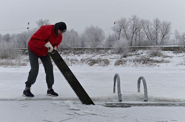 Muž vysekává díru v ledu na řece Irtyš během zahájení zimní plavecké sezóny v ruském Omsku. - Sputnik Česká republika