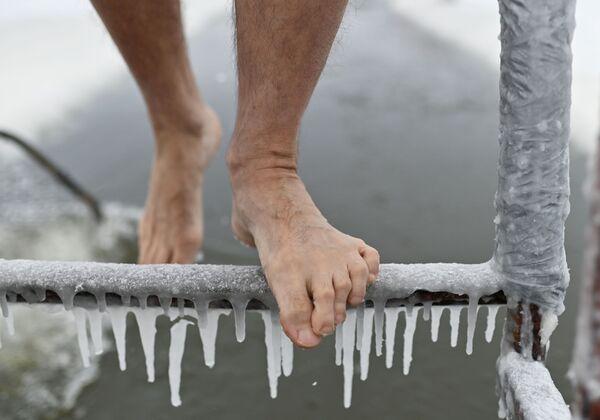 Muž na zmrzlém žebříku v den zahájení zimního plavání v Omsku v Rusku. - Sputnik Česká republika