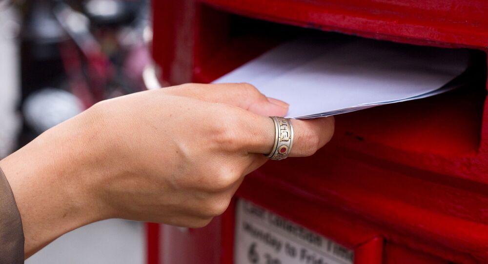 Žena dává dopisy do poštovní schránky
