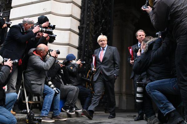 Britský premiér Boris Johnson (C) na ulici Downing Street 10 v Londýně po týdenní schůze kabinetu, na které v důsledku zesíleného šíření onemocnění covid-19 bylo rozhodnuto o zahájení největšího vakcinačního programu v historii země - Sputnik Česká republika
