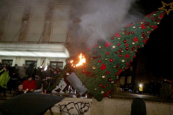 Demonstranti spalují vánoční stromek před budovou premiéra Albánie při střetech v Tiraně - Sputnik Česká republika