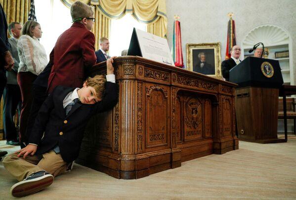 Šestiletý vnuk amerického sportovce Dana Gablea se přitiskl ke stolu během vystoupení jeho dědečka v Bílém domě, Washington - Sputnik Česká republika