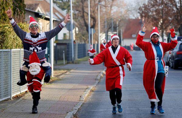 Muži v kostýmech Santa Clausů během běhu o berlu svatého Mikuláše v Berlíně, Německo - Sputnik Česká republika