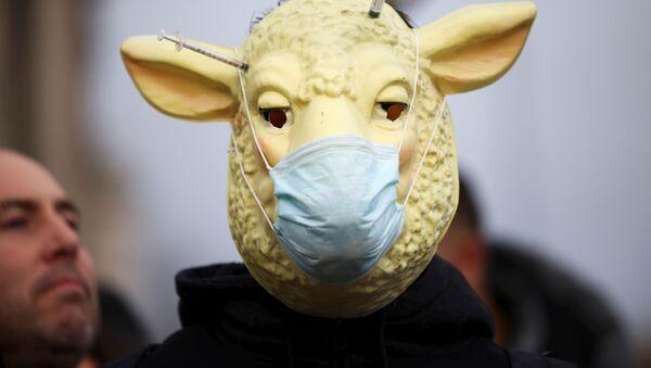 Člověk, skrývající se pod maskou s rouškou, se účastní demonstrace proti očkování na Parlamentním náměstí v Londýně. - Sputnik Česká republika