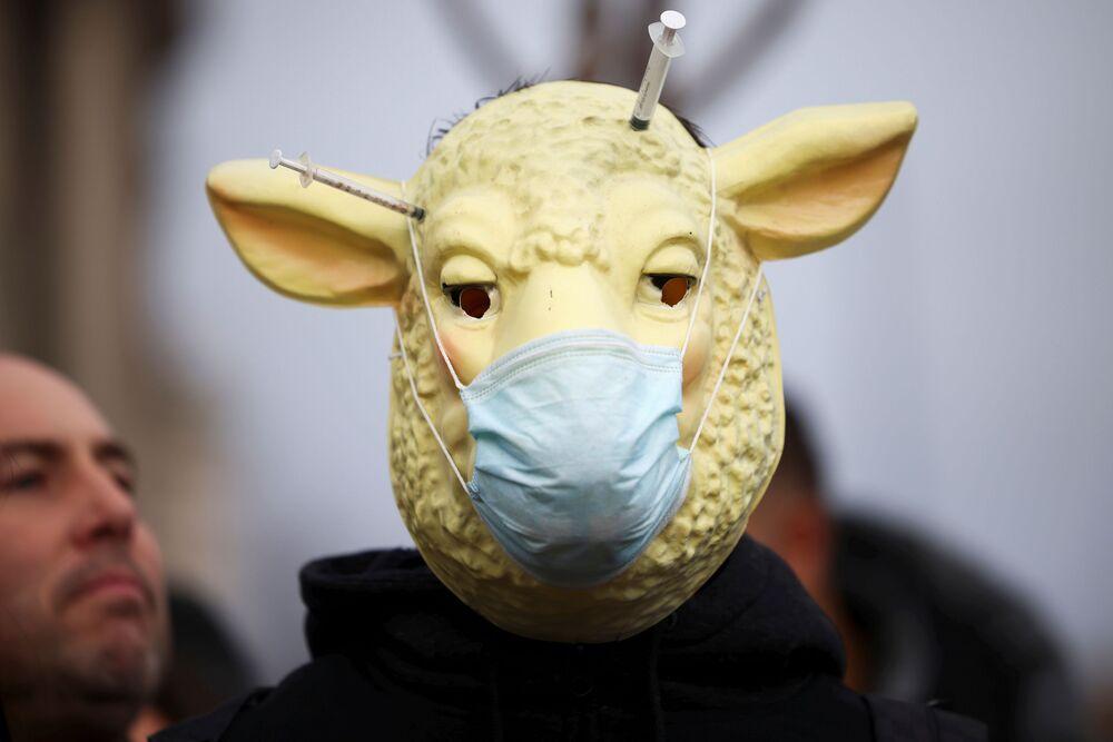 Člověk, skrývající se pod maskou s rouškou, se účastní demonstrace proti očkování na Parlamentním náměstí v Londýně.