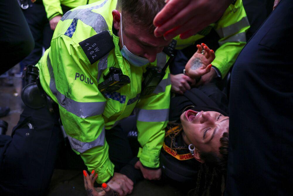 Policista zadržuje aktivistku vystupující proti očkování na Parlamentním náměstí v Londýně.