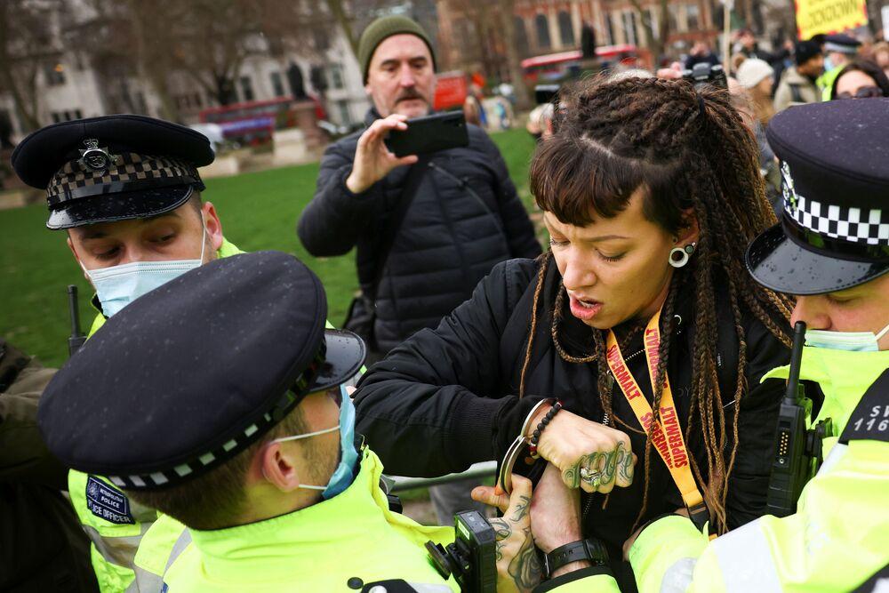 Policista zatýká ženu, demonstrující proti očkování na Parlamentním náměstí v Londýně.
