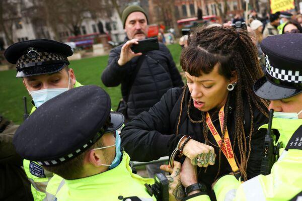 Policista zatýká ženu, demonstrující proti očkování na Parlamentním náměstí v Londýně. - Sputnik Česká republika