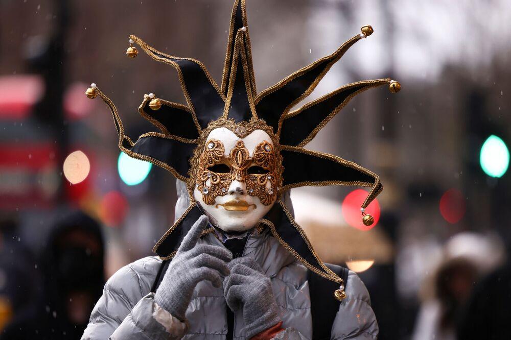 Člověk v karnevalové masce během demonstrace proti očkování.