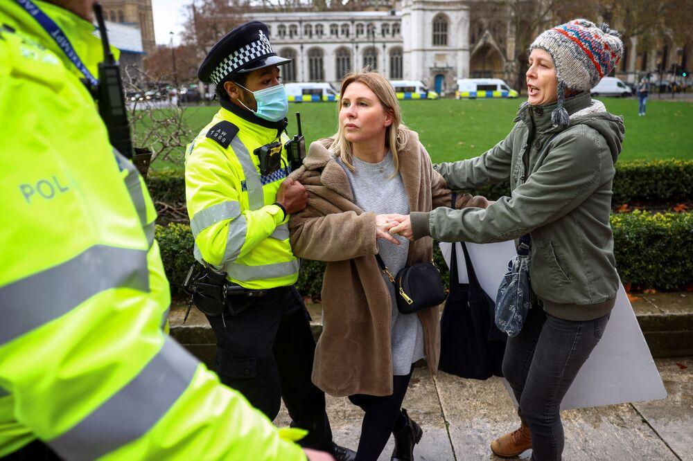 Policista se snaží zadržet aktivistku protivakcinační demonstrace na Parlamentním náměstí v Londýně.