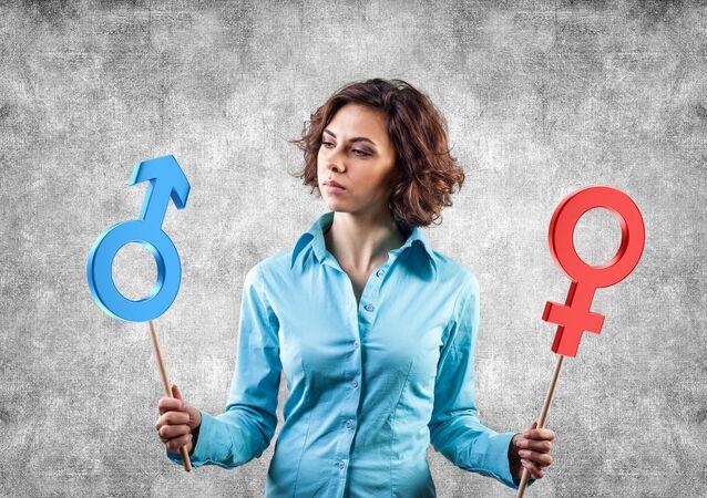Dívka drží v rukou cedule označující pohlaví