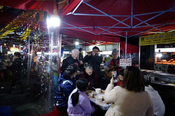 Návštěvníci pouliční restaurace v noci ve Wu-chanu - Sputnik Česká republika