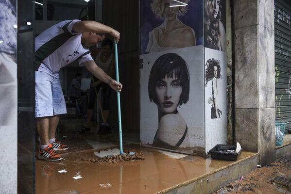 Muž odstraňuje nečistoty z obchodu po záplavách v Belo-Horizonte Brazílie - Sputnik Česká republika