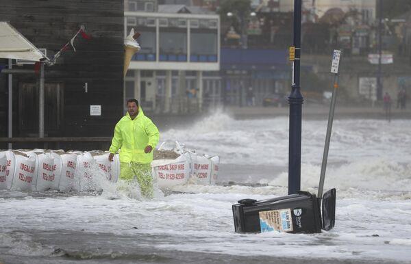 Muž na zaplaveném nábřeží v Swanage, Velká Británie - Sputnik Česká republika