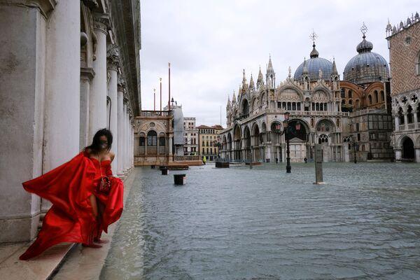 Žena ve vlajících šatech v zaplaveném náměstí Piazza San Marco v Benátkách, Itálie - Sputnik Česká republika