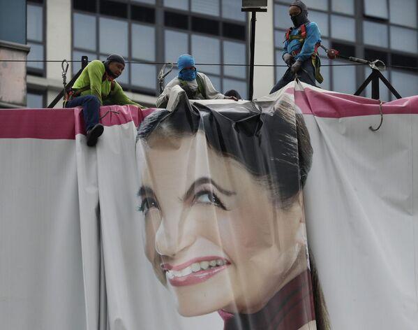 Dělníci skládají reklamní plakát, poté čekají na příchod tajfunu Wongfong, Filipíny - Sputnik Česká republika