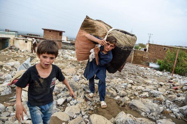 Mladí lidé zachraňují zbytky věcí z trosek domů po náhlých povodních v Charikaru v provincii Parván v Afghánistánu - Sputnik Česká republika