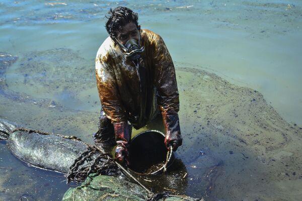 Muž čistí vodu od ropy rozlité u pobřeží Mauricia - Sputnik Česká republika