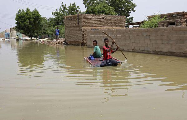 Teenageři plavou na raftu po zaplavené ulici v městě Salmania, Súdán - Sputnik Česká republika