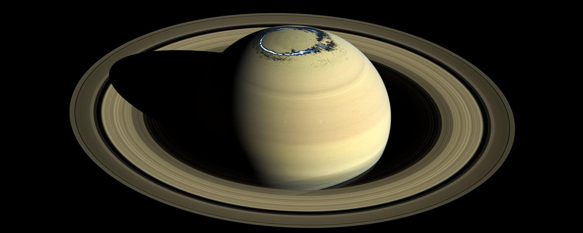 Изображение истинного цвет Сатурна, запечатленного Кассини в 2016 году, наложено на изображение цвета ультрафиолетового сияния в северном полушарии, которое наблюдалось 20 августа 2017 года - Sputnik Česká republika, 1920, 01.08.2021