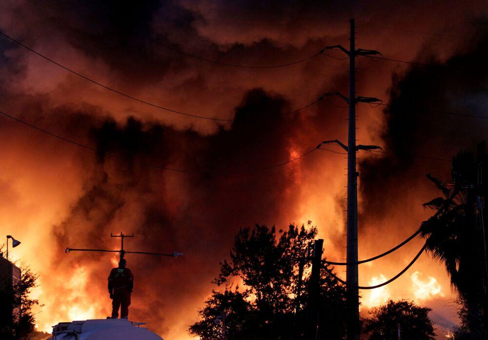 Hasič stojí na vodní nádrži při požáru v závodě na zpracování kovového šrotu Deacero v Guadalupe, na okraji Monterrey, Mexiko