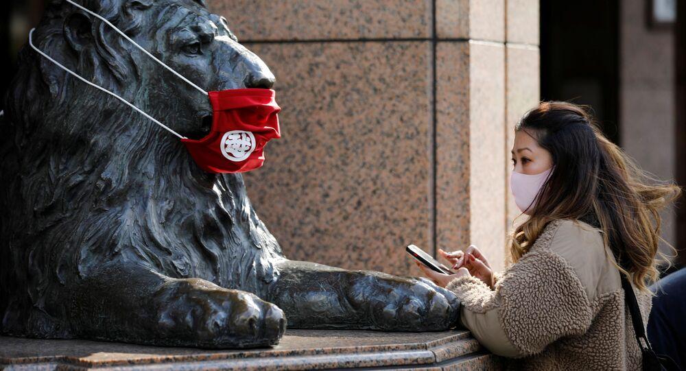 Žena nosí roušku před sochou v Tokiu