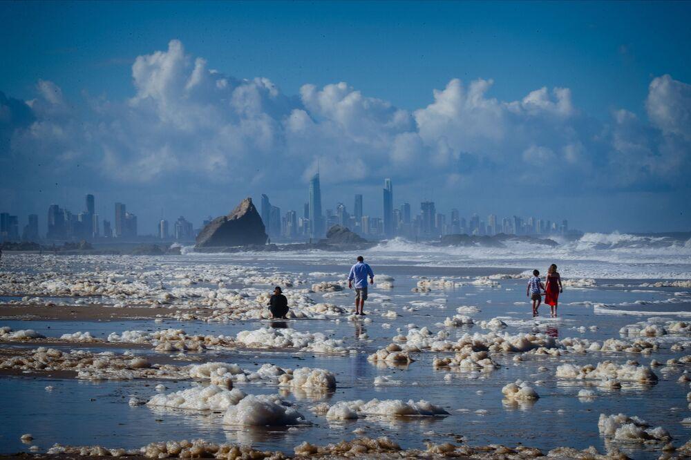 Turisté chodí uprostřed pěny na pláži po cyklónu v Austrálii