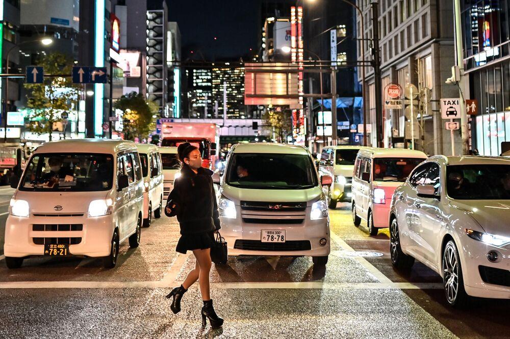 Žena v ochranné masce přechází silnici v Tokiu