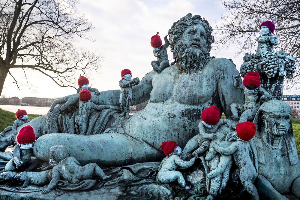 Malé bronzové sochy ve vánočních kloboucích a maskách v Kodani