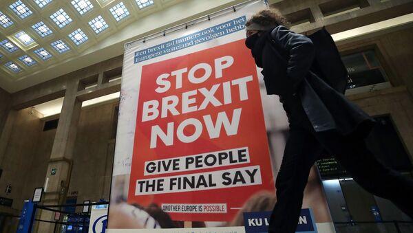 """Žena prochází kolem billboardu zobrazujícího fotografii transparentu s nápisem """"Stop Brexit Now"""" na hlavním nádraží v Bruselu v Belgii 17. prosince 2020 - Sputnik Česká republika"""