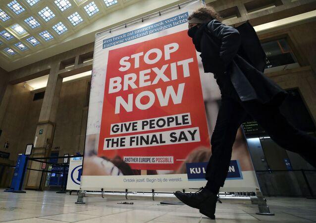 """Žena prochází kolem billboardu zobrazujícího fotografii transparentu s nápisem """"Stop Brexit Now"""" na hlavním nádraží v Bruselu v Belgii 17. prosince 2020"""