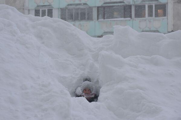 Dítě si hraje ve sněhu ve dvoře bytového domu v Norilsku - Sputnik Česká republika