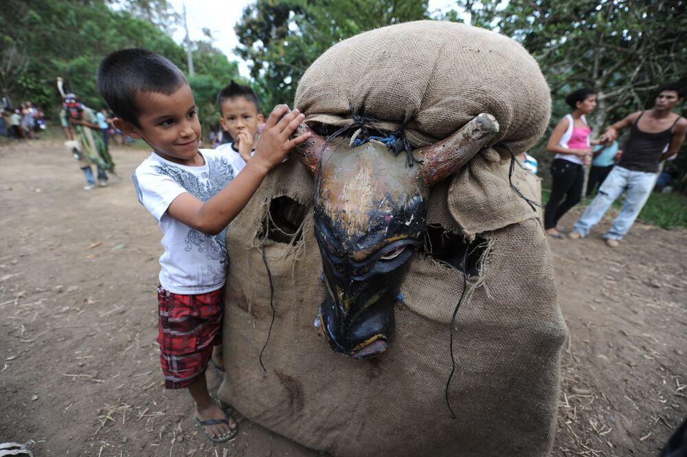 Chlapec si hraje s účastníkem festivalu Feast Of The Devils v kostýmu býka na Kostarice
