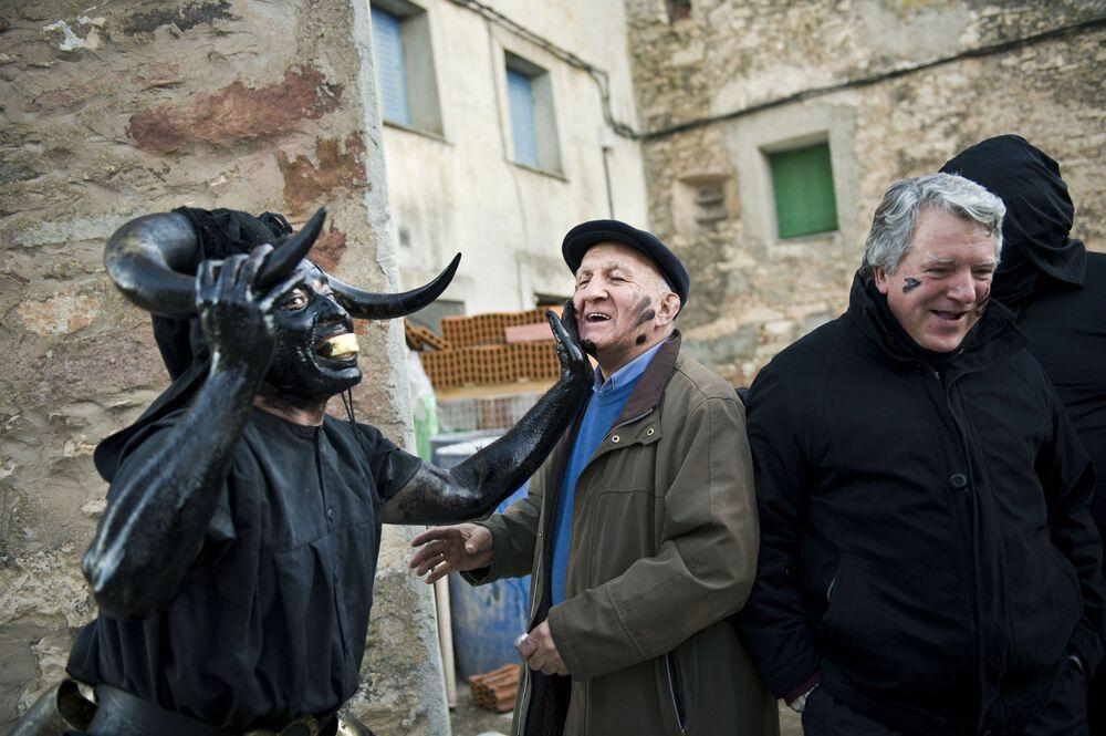 Muž s býčími rohy v ropě a sazích během karnevalu ve Španělsku