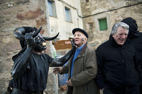 Muž s býčími rohy v ropě a sazích během karnevalu ve Španělsku - Sputnik Česká republika