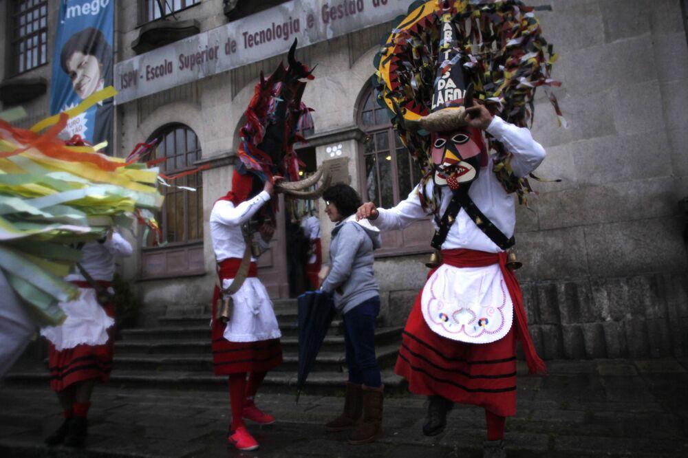 Účastníci festivalu v býčích maskách a tradičních kostýmech v Portugalsku