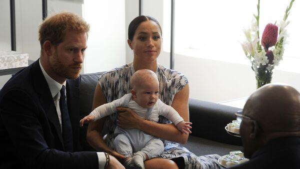 Britský princ Harry a Meghan, vévodkyně ze Sussexu, kteří drží svého syna Archieho, s emeritním anglikánským arcibiskupem Desmondem Tutuem v Kapském Městě v Jižní Africe - Sputnik Česká republika