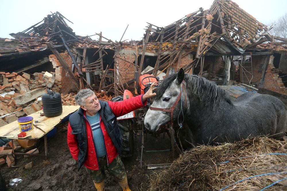 Farmář se svým koněm poblíž zničeného domu po zemětřesení v Chorvatsku.